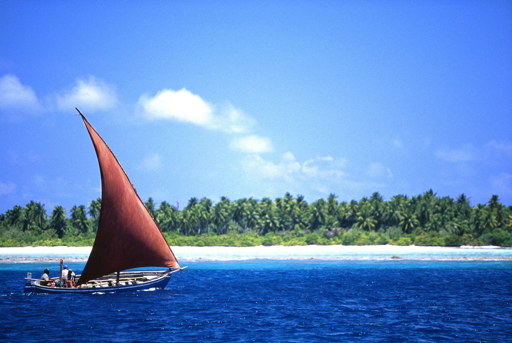 A small local sail boat with a red sail nagivates inside the outer reef, northern Maldives