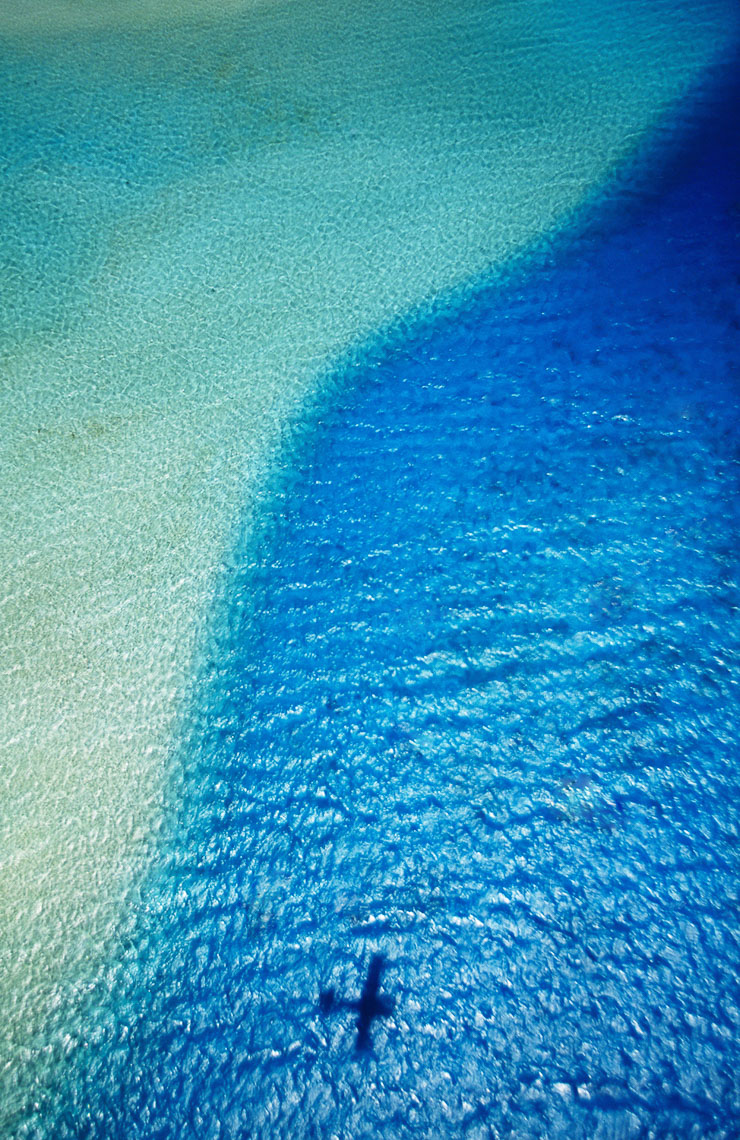 Aerial view of the shadow of my plane mid lagoon , Rangiroa, French Polynesia