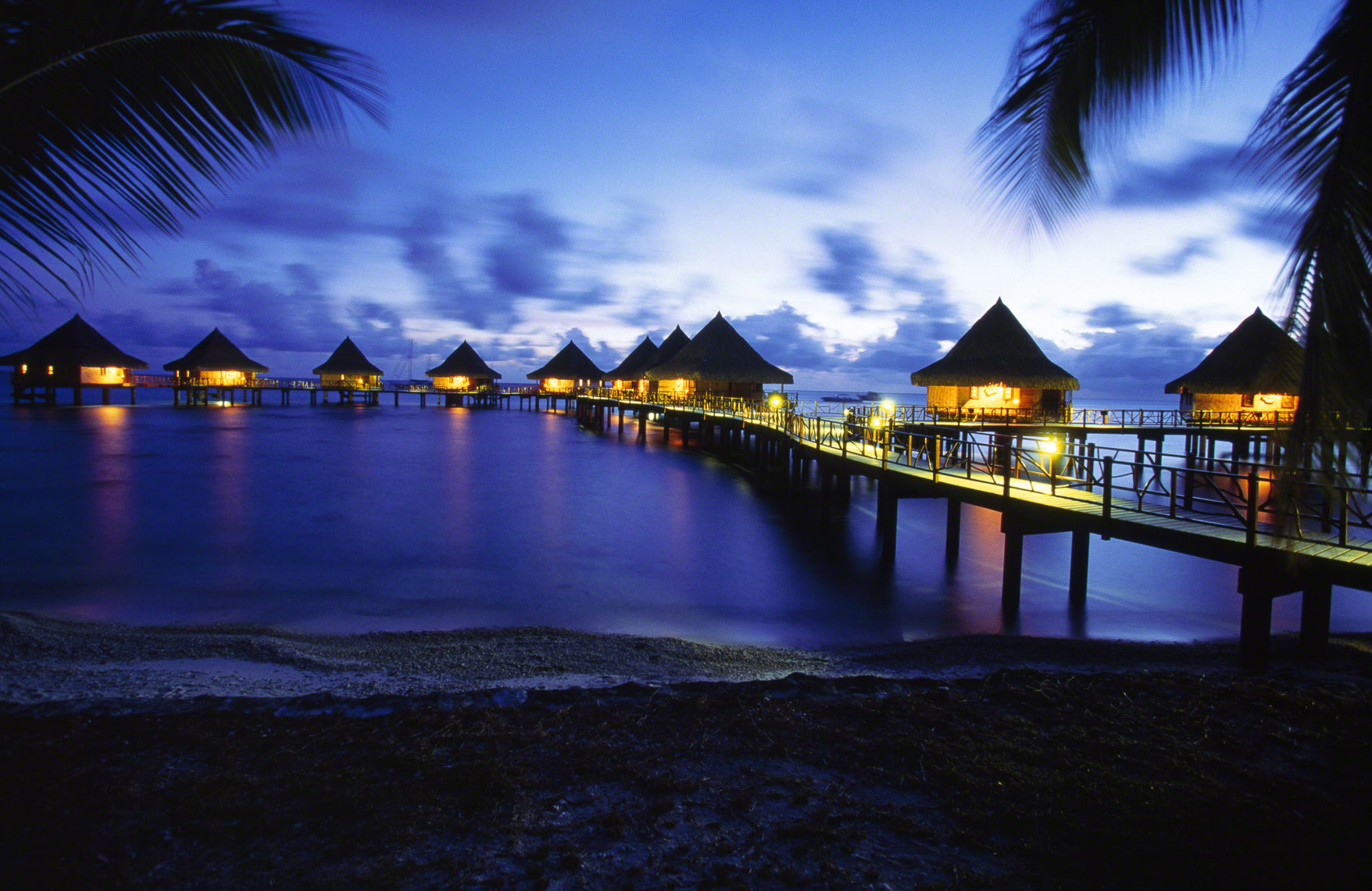 Over the water bungalows of the Kai Ora resort at dusk